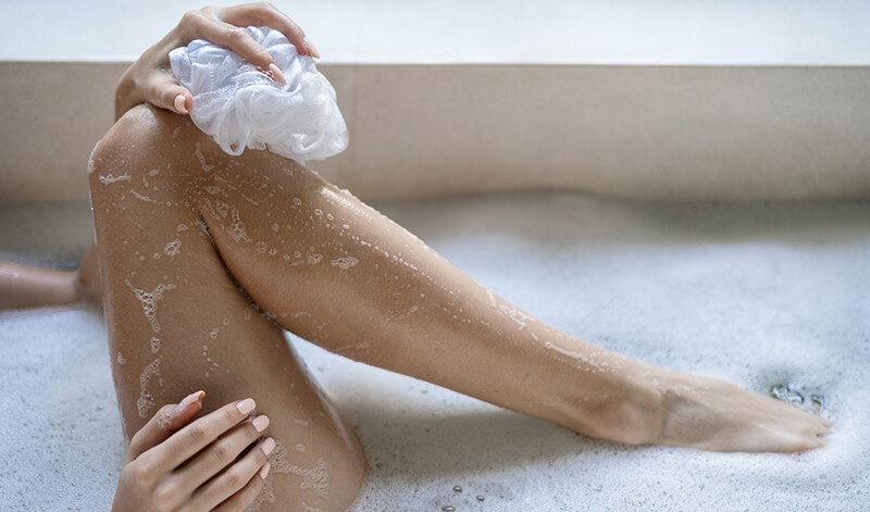 Woman washing her leg in the tub as part of winter leg care routine