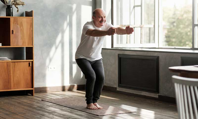 yoga stretch chair pose, Man doing yoga indoors - A Chair pose